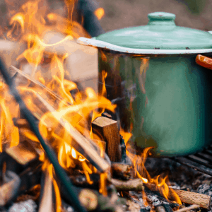 Cooking over fire with colourful enamel pots and pans