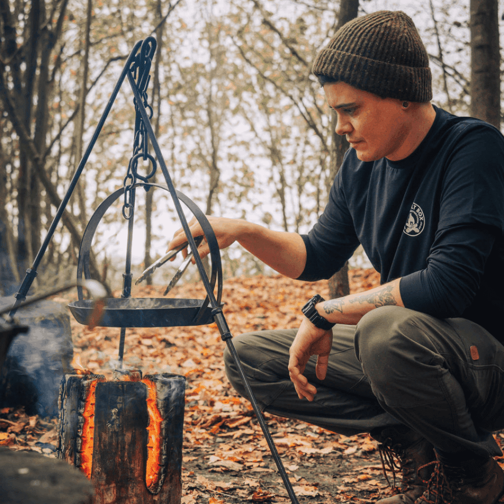 Christian cooking with a dutch oven over fire
